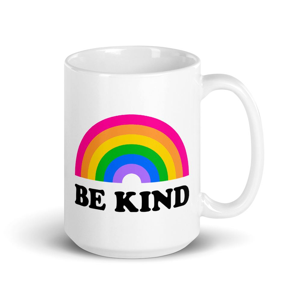tall white mug with text that says be kind and a rainbow above it