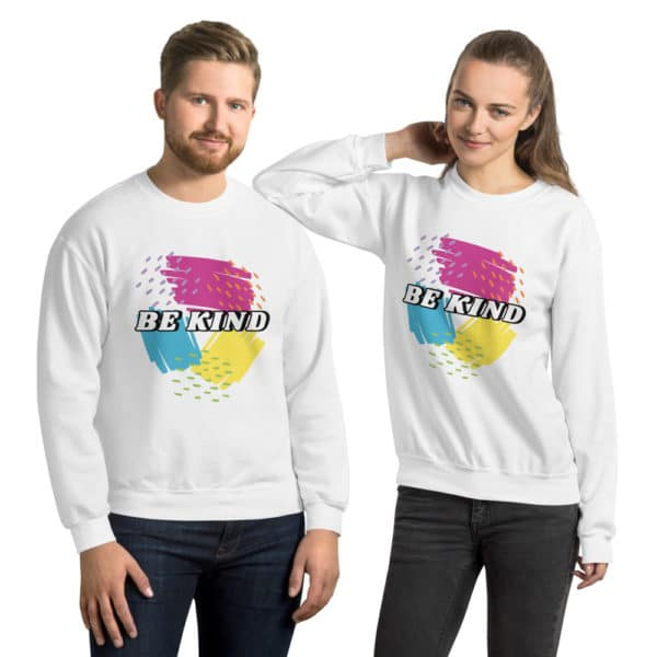two people wearing white sweatshirts with pink, yellow, and blue scribbles that says be kind