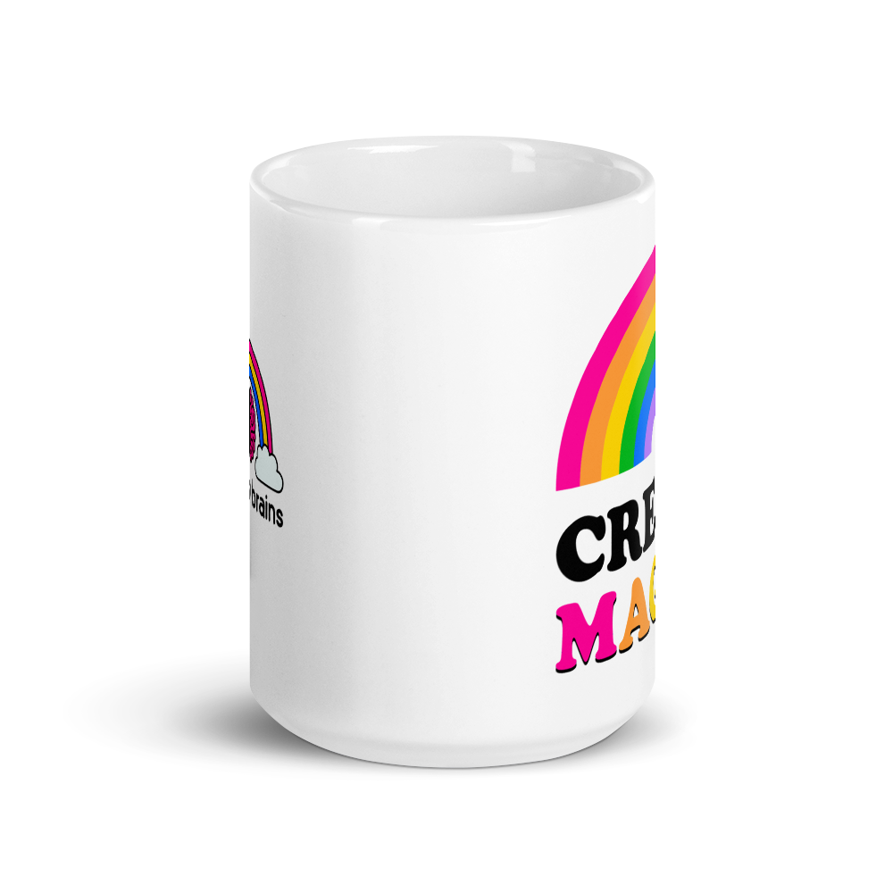 the side of a white mug that says create magic with a rainbow and colorful sparkles