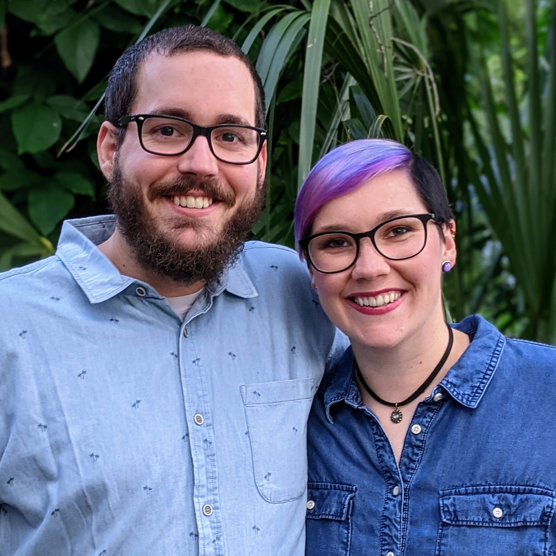 Michael and Taylor, co-founders of Rainbow Brains smiling in front of foliage